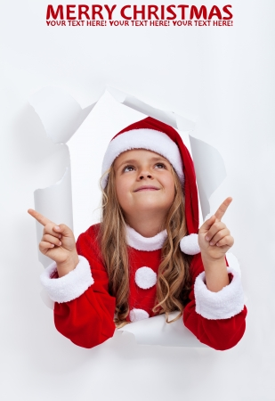 Happy smiling santa girl at christmas time pointing upwards to copy space photo
