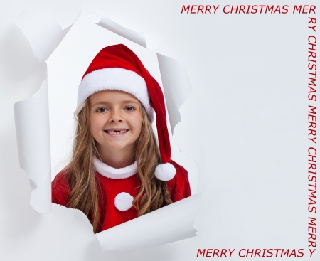 Happy little santa girl with teeth missing, smiling through hole - copy space photo