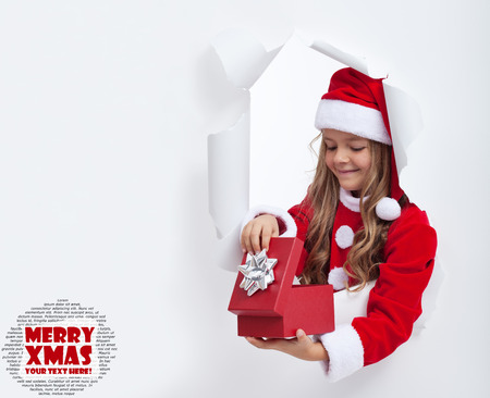 Little girl opening christmas present - with lots of copy space photo