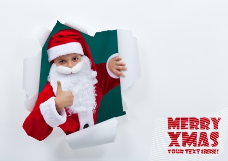 popping out: Santa popping out of torn edges hole with thumbs up sign - copy space Stock Photo