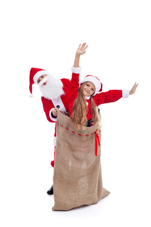 Santa Claus surprised by helper popping out of the bag - isolated photo