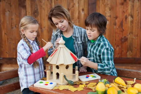 care providers: Woman with kids in autumn painting the bird house - preparing it for winter time