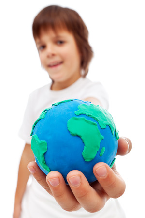 The world in my hand - young boy holding earth globe made of clay photo