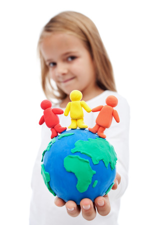 A world of harmony concept with little girl holding earth globe and people made of clay