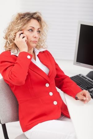 mujer decepcionada: Mujer de negocios decepcionado por una conversaci�n telef�nica - sentado en su escritorio Foto de archivo