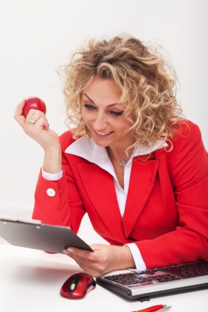 Happy business woman or office worker reading a memo sitting by her desk photo
