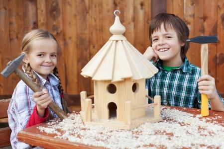 Heureux les enfants la construction d'une maison d'oiseau - souriant et tenant des marteaux