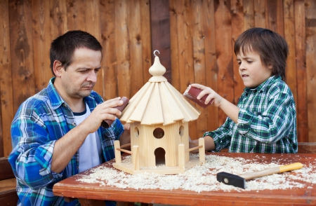 birdhouse: Father and son working on bird house together polishing it with sand paper Stock Photo
