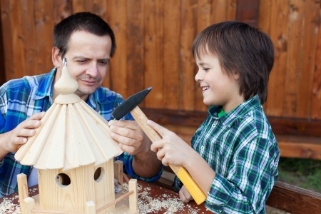 feeder: Father and son building a bird house or feeder for the winter time
