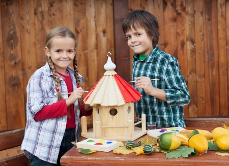 care providers: Kids painting the bird house preparing for winter - environmental awareness concept