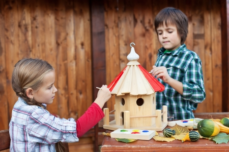 Kids painting the bird house for the winter - care for nature concept photo