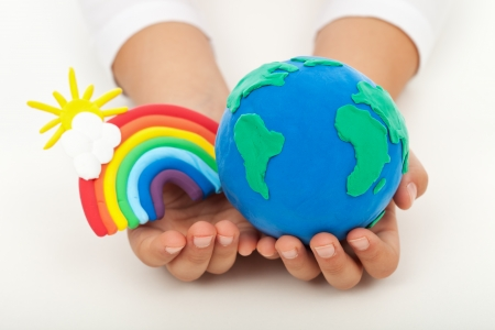 environmental awareness: Ecology concept - a clean earth in child hands with colorful rainbow made of clay
