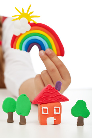 clay craft: Clean environment concept - child hand holding colorful figures made of clay