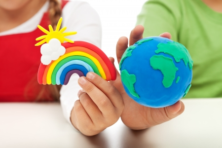 Environmental awareness and education concept - child hands holding earth globe and rainbow made of clay Foto de archivo