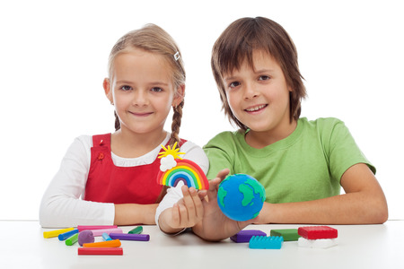 Kids making colorful ecology theme clay figures - holding earth globe and rainbow photo