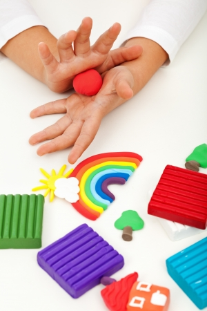 clay craft: Child playing with colorful clay molding different shapes - closeup on hands