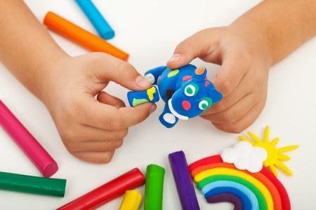 Dziecko bawi się z kolorowych figur zwierząt podejmowania gliny - zbliżenie na ręce