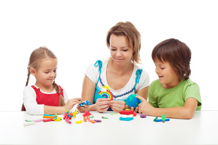 sculpt: Woman and kids playing with colorful clay molding different shapes Stock Photo
