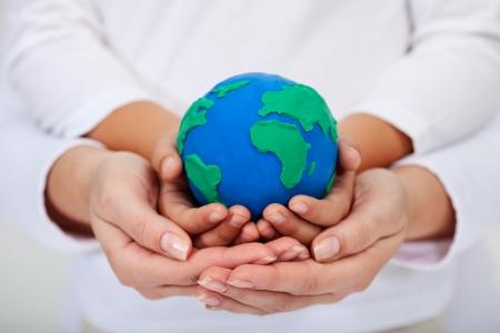 niños reciclando: Nuestro legado para las próximas generaciones - un medio ambiente limpio, con niños y adultos manos sosteniendo el planeta tierra