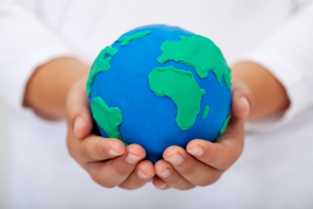 Our home - child holding earth globe made of clay photo