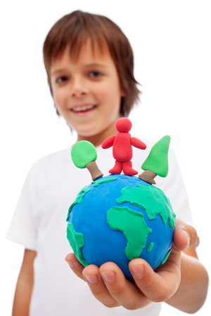 Life in harmony with nature concept - boy holding earth globe with trees and man made of colorful clay photo