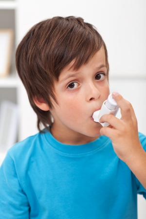 Boy using inhaler for respiratory system issues photo