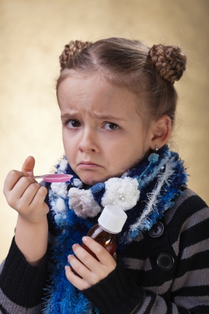 tonsillitis: Little girl does not like cough syrup or medicine