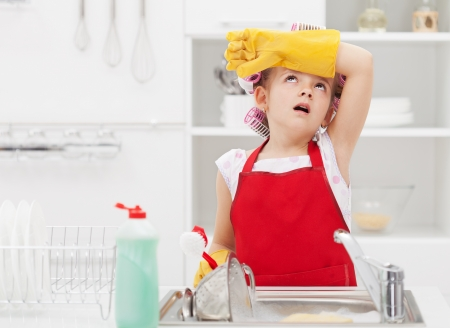 Little housekeeping fairy girl tired of home chores - doing the dishes Standard-Bild