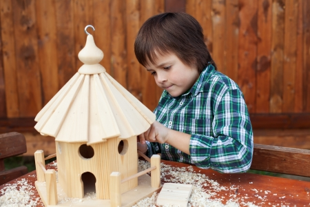 finishing touches: Little boy making the last finishing touches on a wooden bird house he is building Stock Photo