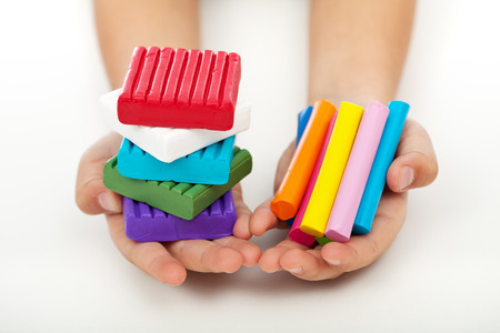 clay modeling: Child hands holding colorful modeling clay bars and blocks Stock Photo