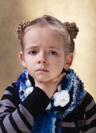 sore throat: Little girl with sore throat looking sad