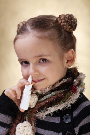 Little girl with nasal spray - fighting cold and the flu photo