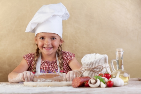 little dough: Happy chef little girl stretching the dough - with food ingredients on the side of table Stock Photo