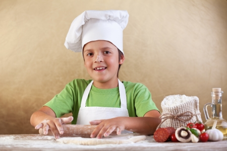 smeary: Baker chef boy stretching the dough smeary with flour