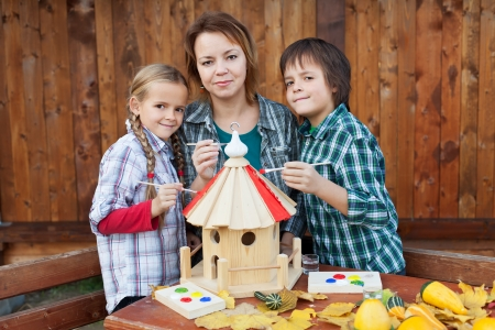 bird feeder: Woman with two kids preparing a bird house for the winter Stock Photo