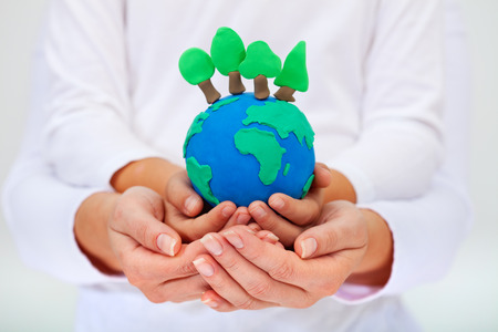 Protecting our environment concept - clay earth with trees held by child and adult hands photo