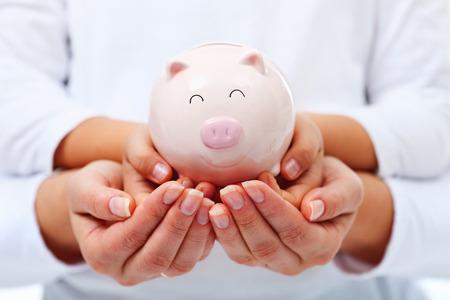 ahorros: Concepto de educación financiera - para adultos y niños las manos sosteniendo sonriendo alcancía Foto de archivo