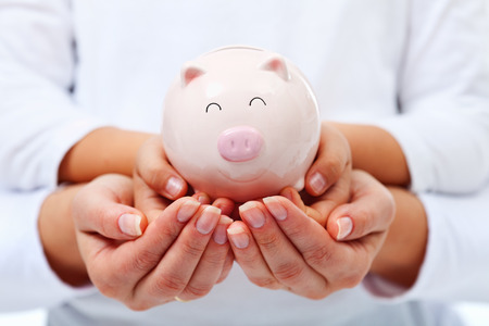 Financial education concept - adult and child hands holding smiling piggy bank Stock Photo