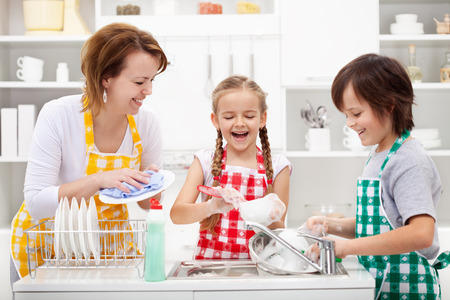 household tasks: Kids and mother washing dishes - having fun together in the kitchen