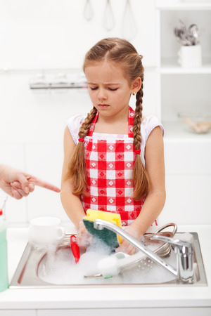 Do the dishes this instant - sad and grumpy little girl ordered to wash up tableware photo