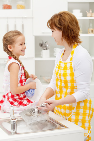 Mother and daughter washing the dishes together and talking photo
