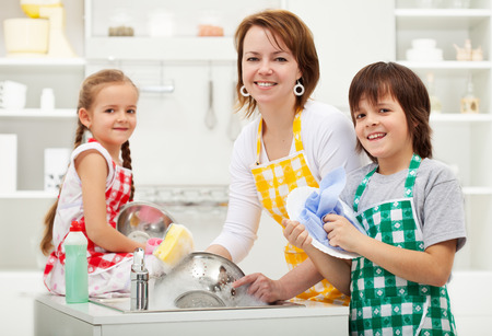 household tasks: Kids helping their mother in the kitchen - washing the dishes together Stock Photo