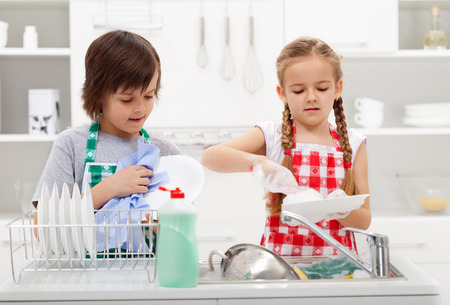 tasks: Kids washing the dishes in the kitchen together - helping out with the home chores Stock Photo