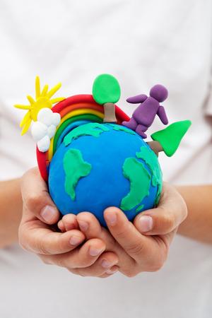 아이의 손에 무지개 나무와 점토 지구를 모델링