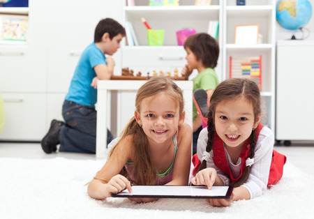 kid smiling: Kids playing classic board games versus modern tablet computer games