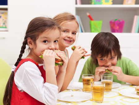 Three kids chomping on healthy sandwiches with cheese and vegetables photo