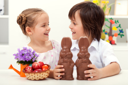 Happy kids at easter time laughing - with large chocolate bunnies and colorful eggs Stock Photo