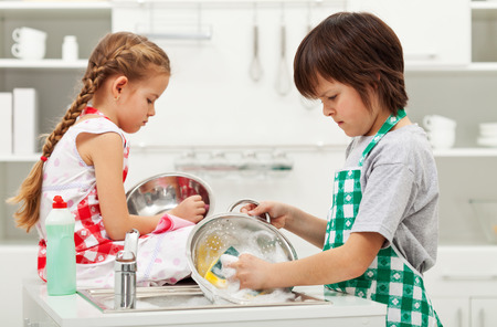 doing chores: Grumpy kids doing home chores on parents order - washing dishes