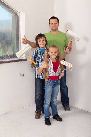moving activity: Kids with their father preparing to paint the room in their new home Stock Photo