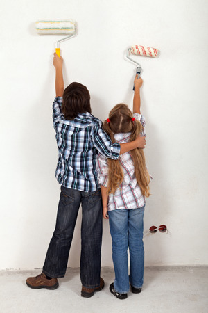 Kids painting the room in their new home using paint\ rollers